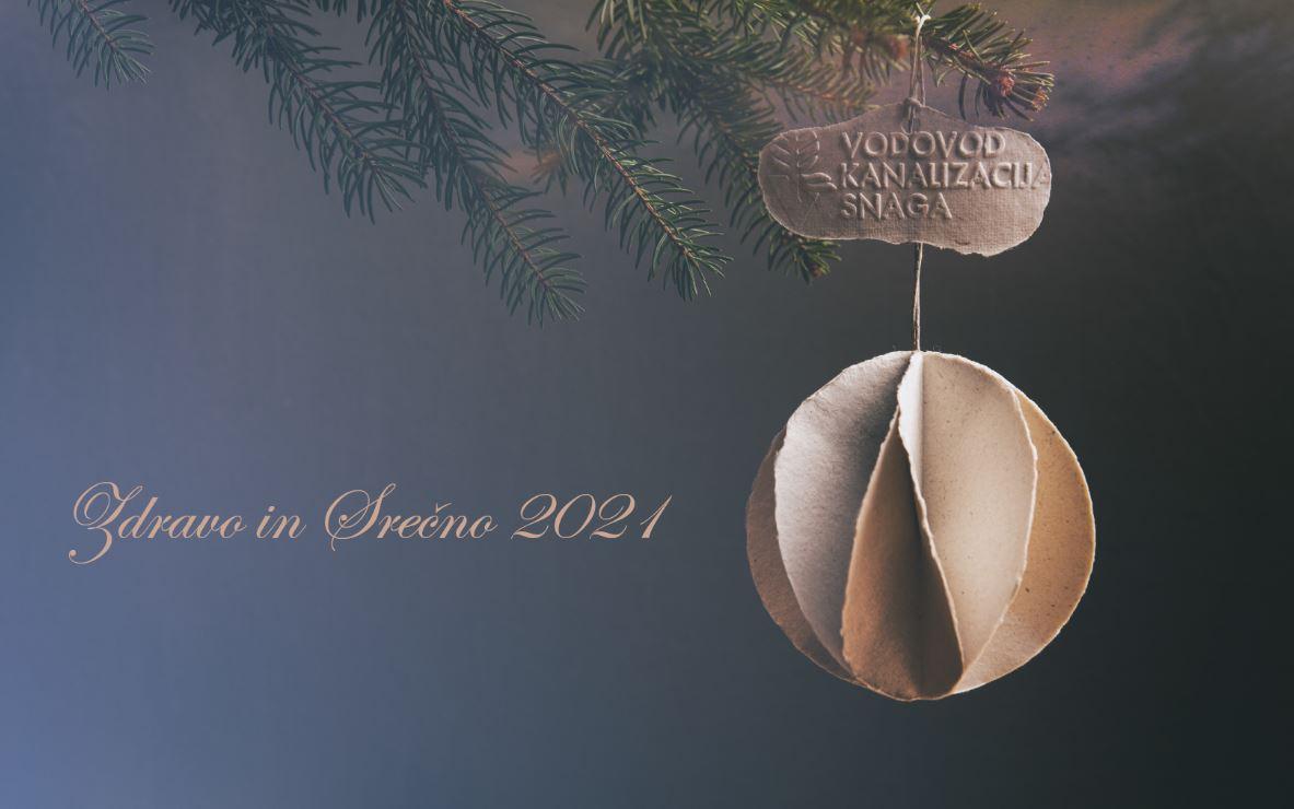 """Na fotografiji je papirnat novoletni okrasek, ki visi z veje. Zraven je zapisano voščilo: """"Zdravo in srečno 2021!"""""""